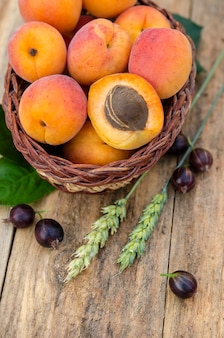Köstliche reife aprikosen und beeren auf rustikalem hintergrund. gesunde lebensmittel