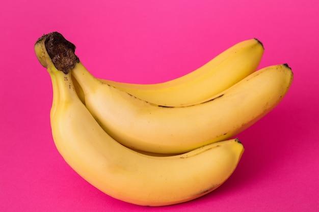 Köstliche reife bananen auf rosa hintergrund
