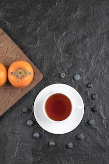 Köstliche reife fuyu-kakis auf holzbrett mit tasse tee