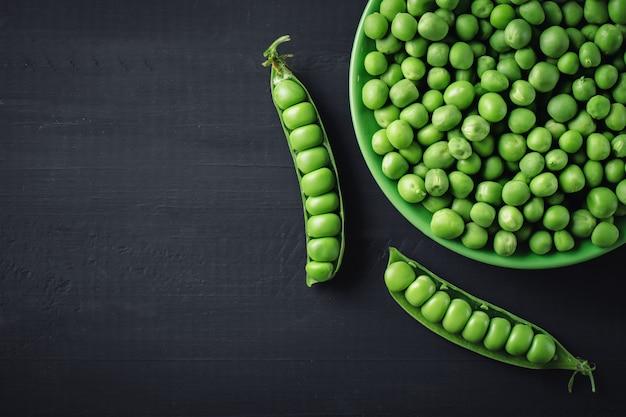 Köstliche reife grüne erbsen, die auf einem holztisch liegen.