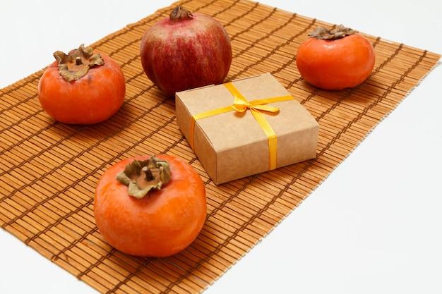 Köstliche reife kaki und granatapfelfrüchte mit einer geschenkbox auf der bambusserviette. bio-früchte.