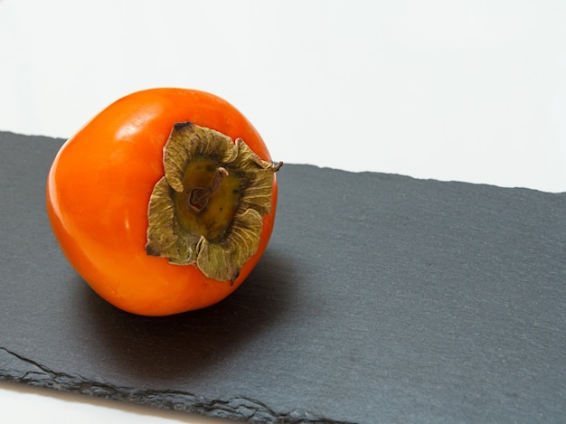 Köstliche reife kakifrucht auf dem schwarzen steinschneidebrett. bio-früchte.