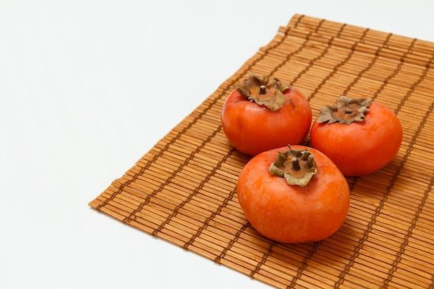 Köstliche reife kakifrüchte auf der bambusserviette. bio-früchte.