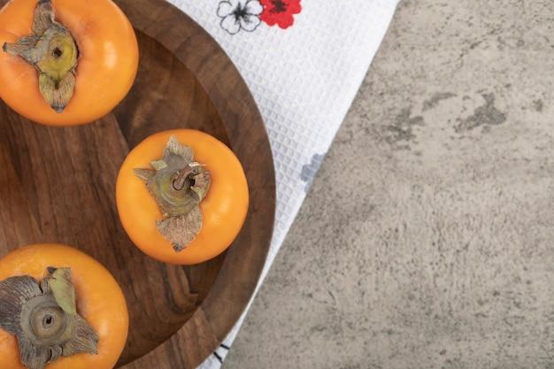 Köstliche reife kakifrüchte auf holzteller gelegt
