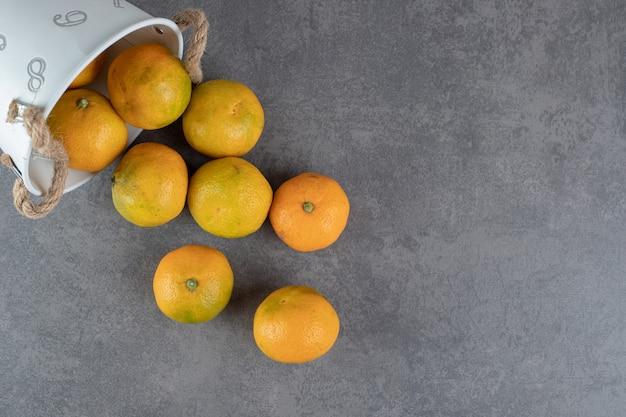 Köstliche reife mandarinen aus dem eimer auf marmorhintergrund. foto in hoher qualität