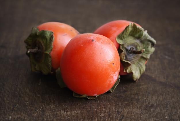 Köstliche reife orange kakis auf holztisch Premium Fotos