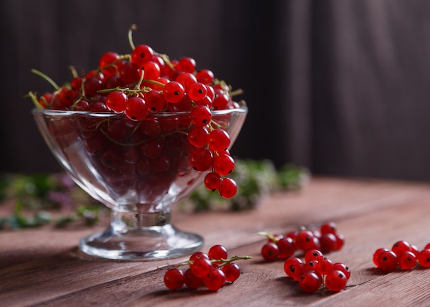 Köstliche reife rote johannisbeere in einem glasvase auf einem holztisch