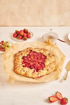 Köstliche rhabarber-erdbeer-gallate-kuchen mit zutaten auf einem weißen tisch