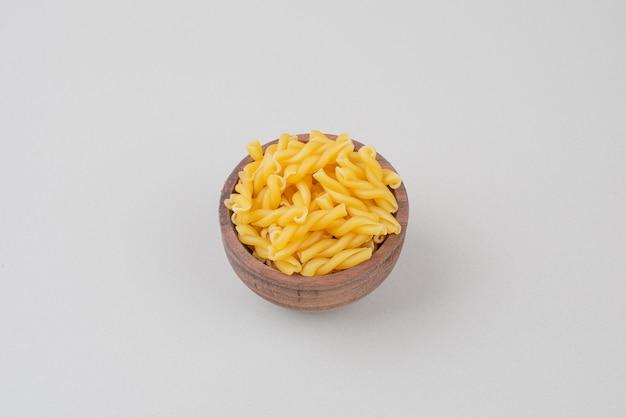 Köstliche rohe makkaroni auf holzteller