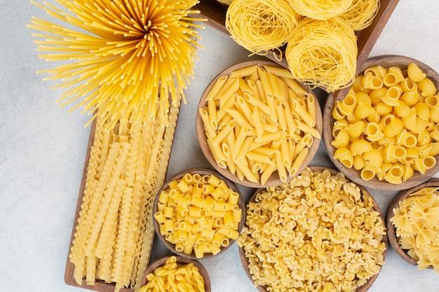 Köstliche rohe makkaroni und fadennudeln auf holzschalen