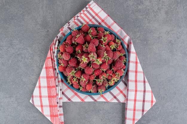 Köstliche rote himbeeren auf blauem teller. foto in hoher qualität