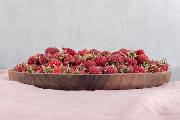 Köstliche rote himbeeren auf holzplatte. foto in hoher qualität