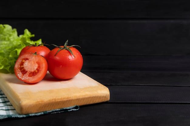 Köstliche rote tomaten auf holzbrett gelegt. hochwertiges foto