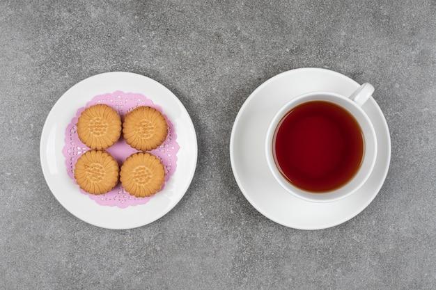 Köstliche runde kekse und eine tasse tee auf marmoroberfläche