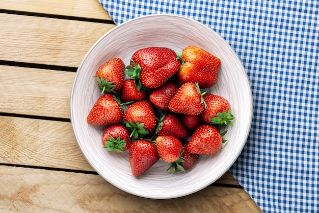 Köstliche saftige erdbeeren auf dem teller mit hölzernem hintergrund.