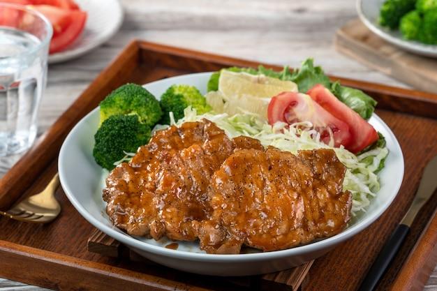 Köstliche saftige schweinekoteletts mit gemüse- und obstsalatmahlzeit in einem teller auf esstisch.