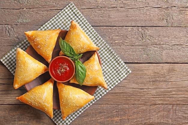 Köstliche samsa mit sauce und basilikum auf einem holztisch. draufsicht