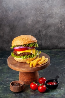 Köstliche sandwich-pommes auf holzbrett tomaten-ketchup-pfeffer auf dunkler mischfarboberfläche