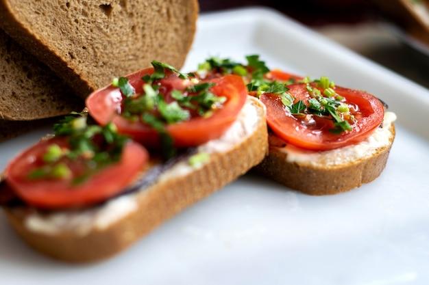 Köstliche sandwiches brauner toast mit frischem gemüse wie rot geschnittenen tomaten und schwarzen gebratenen auberginen mit gemüse oben auf weißem teller