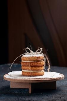 Köstliche sandwichkekse von vorne, die lecker auf dem dunkelblauen schreibtischkuchen gebunden sind