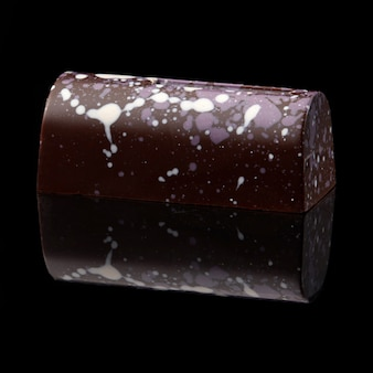 Köstliche schokolade auf schwarzer oberfläche mit reflexion