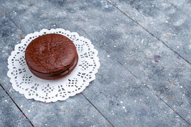 Köstliche schokoladenkuchenrunde gebildet lokalisiert auf grauem, backen schokoladenkuchen-kakaosüßkeks