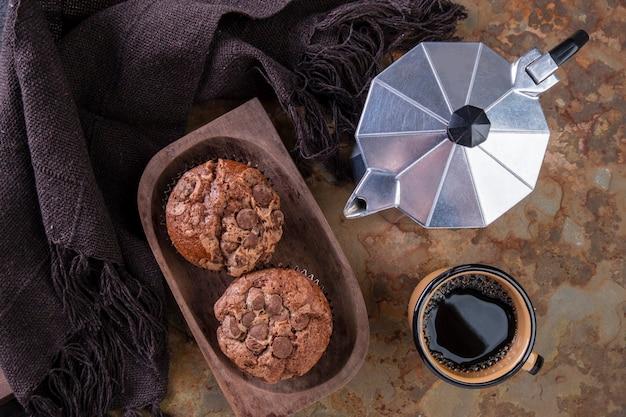Köstliche schokoladenmuffins, eine kaffeetasse und eine traditionelle italienische kaffeemaschine.