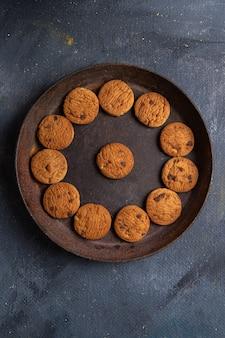 Köstliche schokoladenplätzchen der oberen entfernten ansicht innerhalb der dunklen runden platte auf dem dunklen grauen hintergrundplätzchenkeks süß