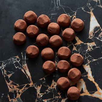 Köstliche schokoladentrüffel auf dunkler marmoroberfläche