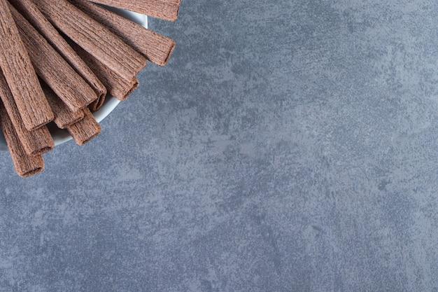Köstliche schokoladenwaffelrolle in einer schüssel auf der marmoroberfläche