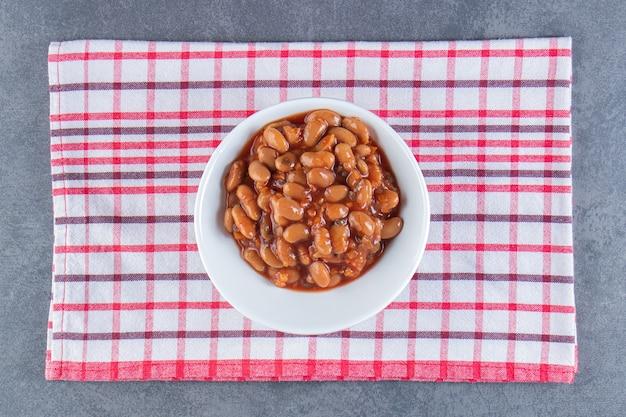 Köstliche schüssel mit gebackenen bohnen auf einem geschirrtuch, auf der blauen oberfläche.