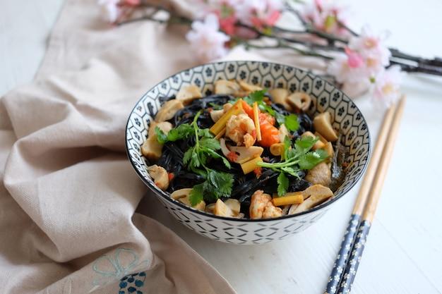 Köstliche schwarze nudeln ramen mit gemüse tofu und fleisch auf der schüssel