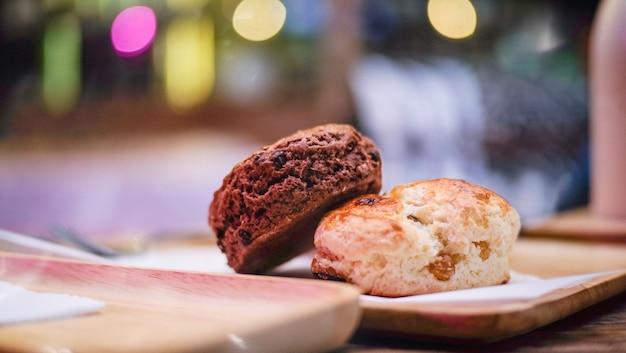 Köstliche scones auf einem hölzernen brett mit unscharfem hintergrund.