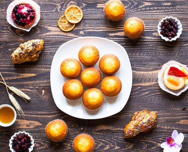 Köstliche selbst gemachte muffins mit joghurt, auf einem holztisch