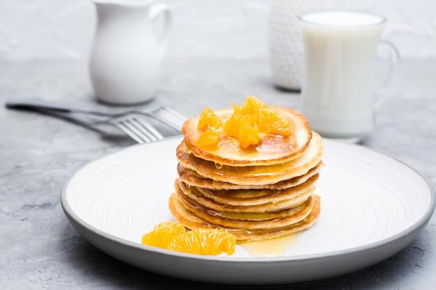 Köstliche selbst gemachte pfannkuchen mit tangerinen und honig, glas milch auf einer platte auf dem tisch