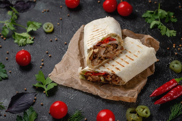 Köstliche shawarma- und lavash-tacos auf einem dunklen steintisch. fastfood-restaurant. gesunde alternative zu fast food. leckere frische wrap-sandwiches mit rindfleisch und gemüse, traditioneller nahost-snac