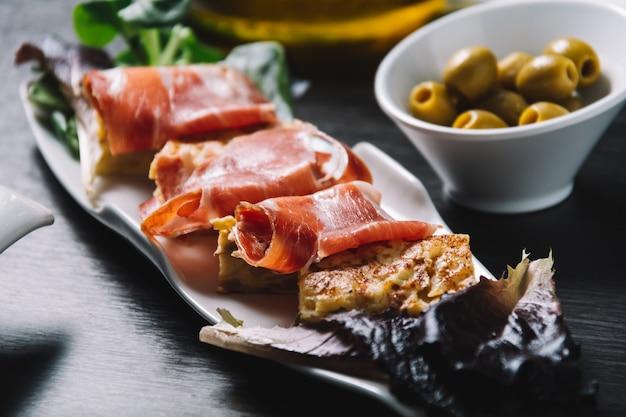 Köstliche spanische kartoffelomelettoberseite mit serranoschinken und oliven
