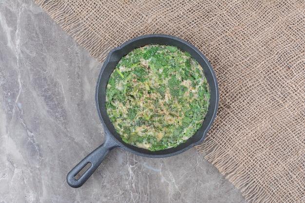 Köstliche spiegeleier mit grün auf dunkler pfanne auf sackleinen. foto in hoher qualität