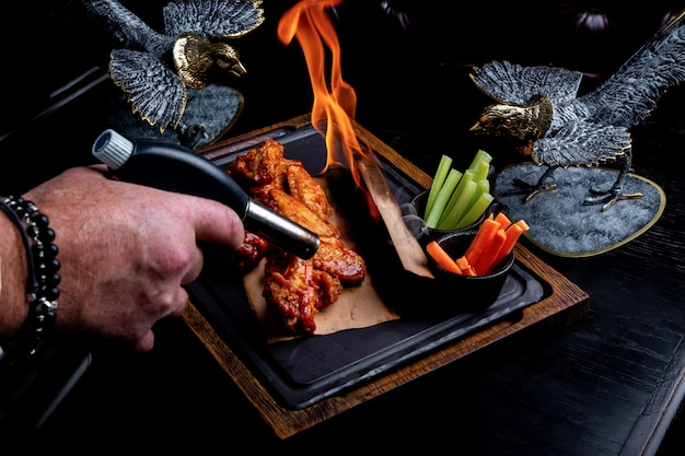 Köstliche stücke hühnerflügel gegrillt mit feuerflammen. auf schwarzem hintergrund des restaurants. barbecue und grillen. restaurant gericht