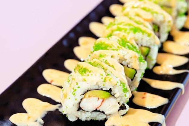 Köstliche stücke von krabben- und avocado-sushi mit soße und grünem fischrogen auf einem teller mit lila hintergrund