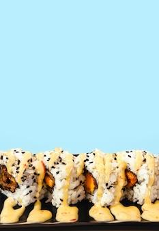 Köstliche stücke von sushi auf einem teller mit soße mit blauem hintergrund und kopierraum