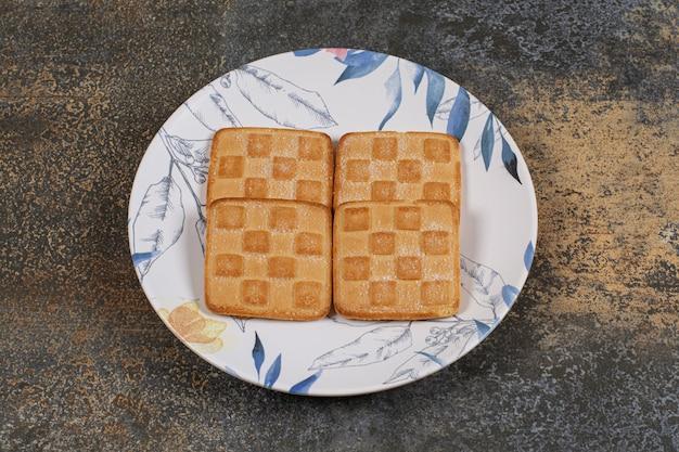 Köstliche süße cracker auf buntem teller.