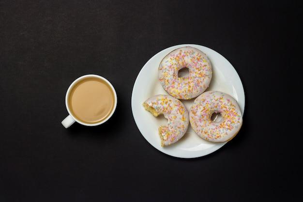Köstliche, süße, frische donuts auf einem weißen teller, eine tasse kaffee, schwarzer hintergrund. konzept von frühstück, fast food, café, bäckerei. flache lage, draufsicht.