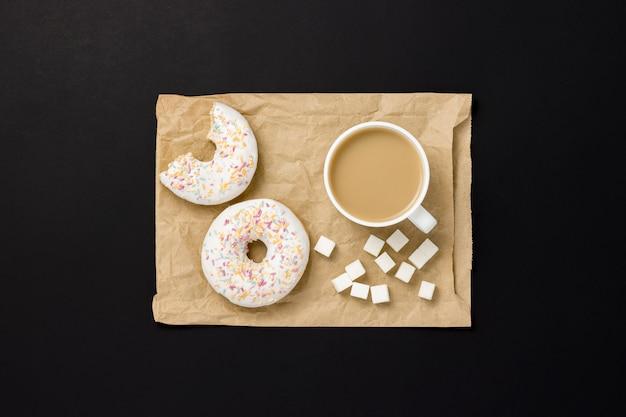 Köstliche, süße, frische donuts, eine tasse kaffee, eine papiertüte zum mitnehmen, schwarzer hintergrund. konzept von frühstück, fast food, café, bäckerei, mittagessen. minimalismus. flache lage, draufsicht.