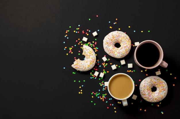 Köstliche, süße, frische donuts, mehrfarbige dekorative süßigkeiten, eine tasse kaffee auf schwarzem hintergrund. konzept von frühstück, fast food, café, bäckerei. flache lage, draufsicht.