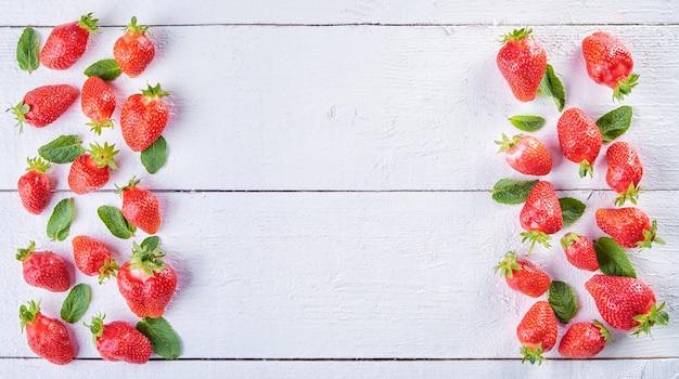 Köstliche süße fruchtmischung von erdbeer- und grünen minzblättern auf weißem holztisch des jahrgangs. heller fruchthintergrund.