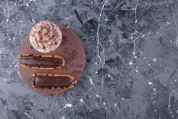 Köstliche süße schokoladen-eclairs und eine tasse kaffee auf einem holzstück.