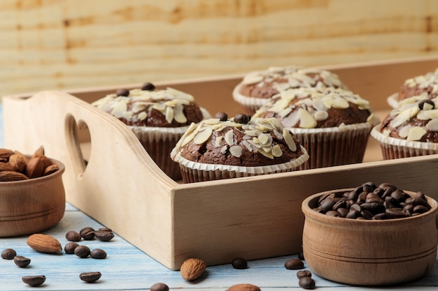 Köstliche, süße schokoladenmuffins mit mandelblüten in einem holztablett neben kaffeekörnern auf einem blauen holztisch.