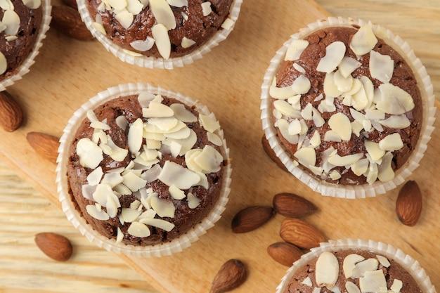 Köstliche, süße schokoladenmuffins mit mandelblüten neben mandelnüssen auf einem natürlichen holztisch. ansicht von oben