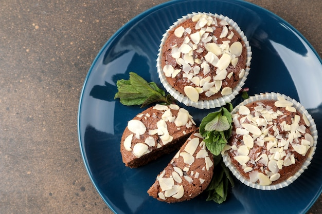 Köstliche, süße schokoladenmuffins mit mandelblüten neben minze und mandeln in einem teller auf einem dunklen tisch. ansicht von oben